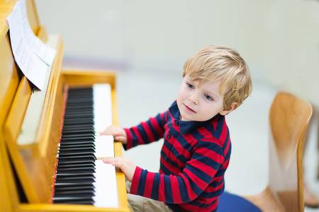 35233005-two-years-old-happy-toddler-boy-playing-piano-early-music-education-for-little-kids-child-at-school