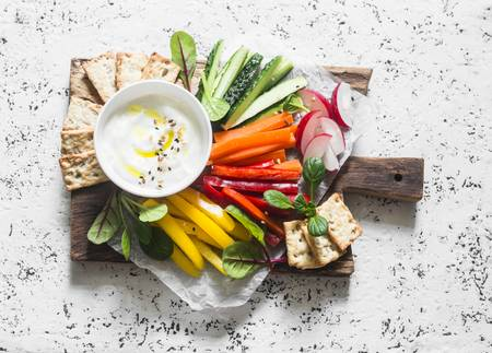 80598146-healthy-snack-raw-vegetables-and-yogurt-sauce-on-a-wooden-cutting-board-on-a-light-background-top-vi