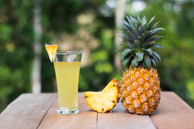 glass-of-pineapple-juice-with-green-nature-background_41058-21