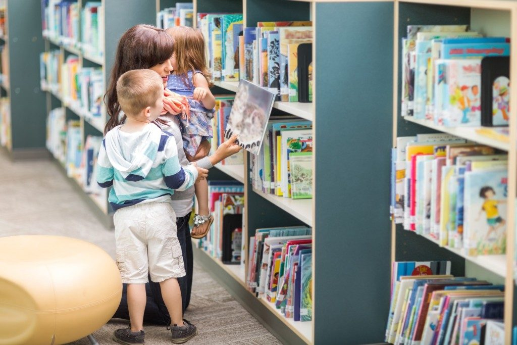 photodune-6701760-teacher-with-children-selecting-book-in-library-m-1024x683